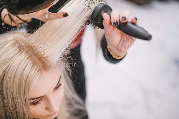 Stilista anonimo che cura i capelli del cliente Foto Gratuite
