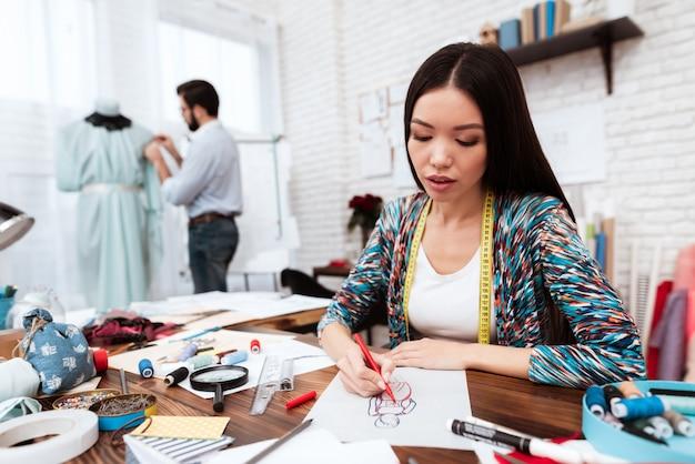 Stilista che disegna modello su carta. Foto Premium