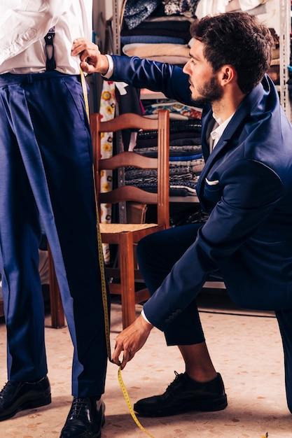 Stilista prendendo la misura dei pantaloni del cliente maschio nel negozio Foto Gratuite