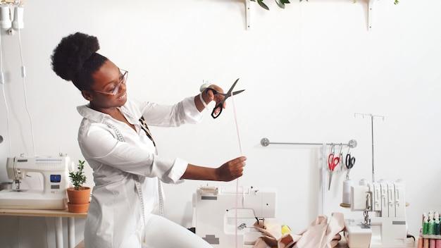 Stilista professionista femminile afroamericano che lavora al tessuto in un'officina Foto Premium