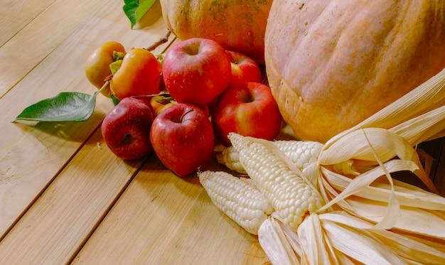 Still life con zucche persimmon mais e mele sul tavolo di legno Foto Premium