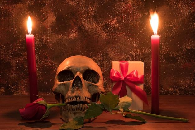 Still life pittura fotografia con cranio umano, presente, rosa e candela sul tavolo di legno Foto Premium