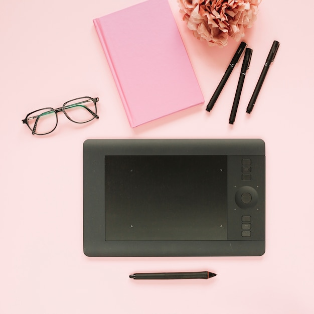 Stilo e tavoletta grafica digitale con elementi decorativi su sfondo rosa Foto Gratuite