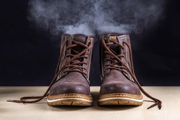 Stivali sporchi con un odore sgradevole. scarpe sudate dopo lunghe camminate e stile di vita attivo. le calzature hanno bisogno di pulizia e rimozione degli odori. cura e lucentezza delle scarpe Foto Premium