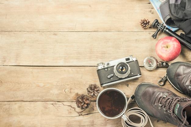 Stivali, zaino, bussola e altri attrezzi da campeggio su una superficie di legno. il concetto di escursioni in montagna o nella foresta, turismo, riposo in tenda, campo. vista piana, vista dall'alto. Foto Premium