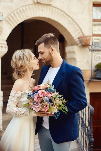 Storia d'amore di una donna e un uomo. abbraccia una coppia di innamorati, una bellissima coppia orientale. un uomo in giacca e una donna in un lungo e lussuoso vestito leggero Foto Premium