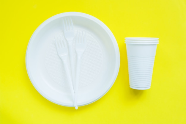 Stoviglie di plastica usa e getta su superficie giallo brillante Foto Premium