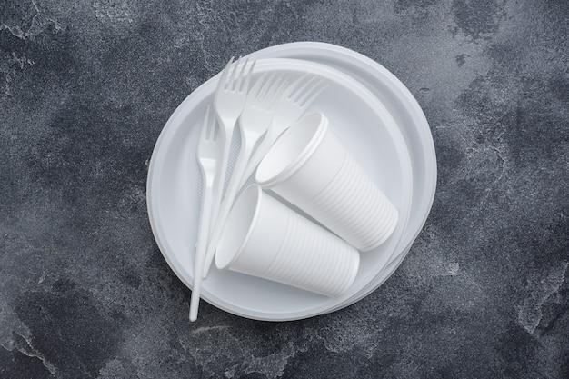 Stoviglie monouso in plastica sul tavolo scuro con spazio di copia. Foto Premium