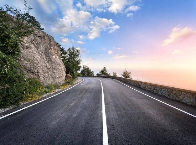 Strada asfaltata nella foresta di estate al tramonto. montagne di crimea Foto Premium