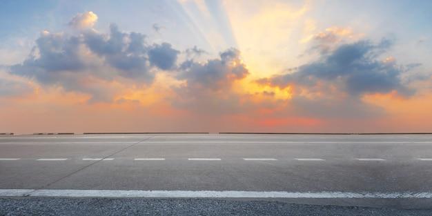 Strada asfaltata vuota dell'autostrada ad alba e penombra Foto Premium