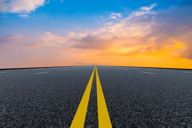 Strada asfaltata vuota e paesaggio naturale nel tramonto Foto Premium