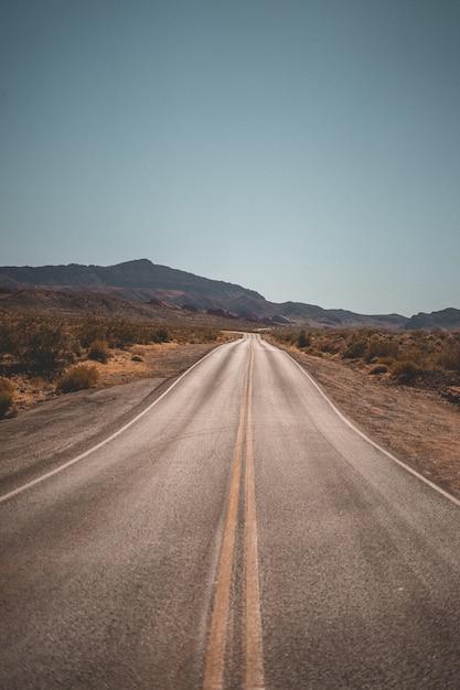 Strada deserta stretta vuota con belle colline sullo sfondo Foto Gratuite