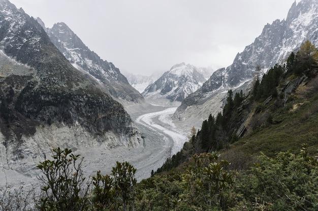 Strada sinuosa in mezzo a montagne innevate sotto un cielo nuvoloso Foto Gratuite