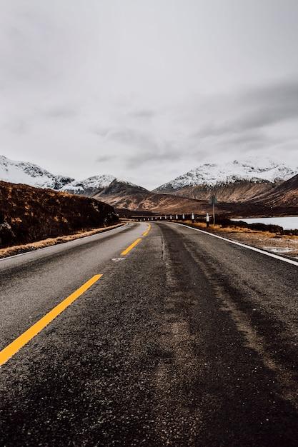Strada solitaria verso le montagne Foto Gratuite