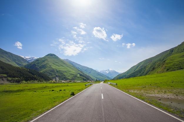 Strada vuota della montagna, colline verdi, cielo soleggiato blu Foto Premium