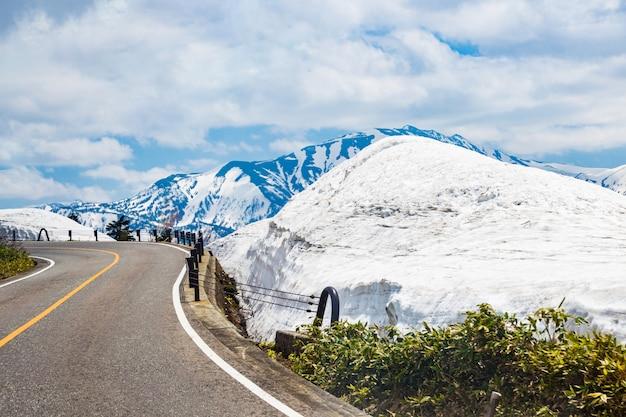 Strade tortuose con neve, montagne e il cielo blu in giappone Foto Premium