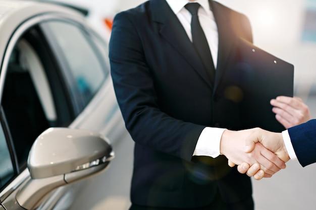 Stretta di mano del venditore e del cliente dell'automobile al concessionario auto Foto Premium