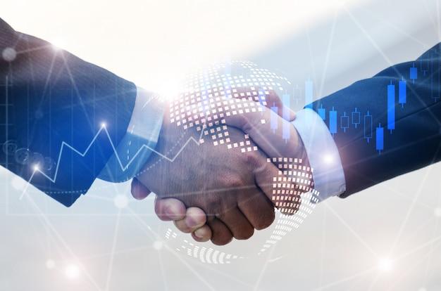 Stretta di mano dell'uomo di affari con il grafico di effetto del mercato azionario forex e dell'ologramma grafico del collegamento di collegamento di rete della mappa di mondo globale Foto Premium