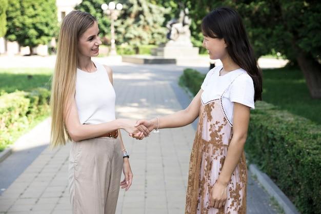 Stretta di mano delle ragazze e guardarsi l'un l'altro Foto Gratuite