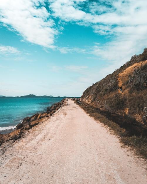 Stretta strada sabbiosa che costeggia il mare e le alte colline ripide con un bel cielo nuvoloso blu Foto Gratuite