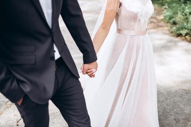 Stringimi e non lasciarmi mai andare. gli sposi felici si tengono per mano Foto Premium
