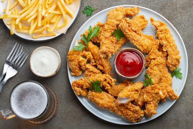 Strisce di pollo impanate con due tipi di salse. Foto Premium