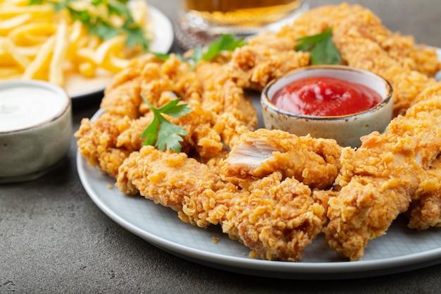 Strisce di pollo impanate con salsa. Foto Premium