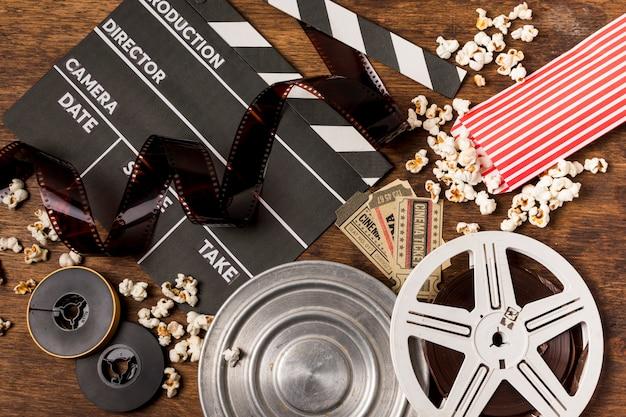 Strisce negative con ciak; bobine di film; biglietti e popcorn sulla scrivania di legno Foto Gratuite