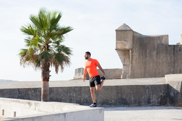 Strong sportivo stretching leg su parapet Foto Gratuite