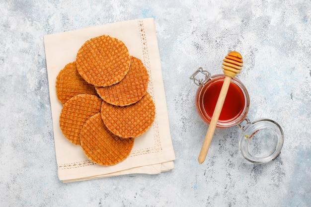 Stroopwafels, cialde al caramello olandesi con tè o caffè e miele su cemento Foto Gratuite