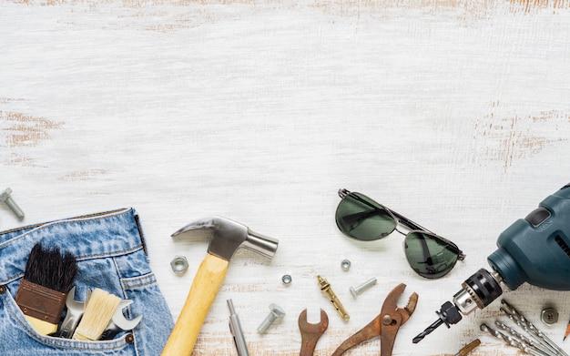 Strumenti e vestiti piani degli accessori di disposizione per il lavoratore su di legno bianco arrugginito con lo spazio della copia. vista superiore dello spazio in bianco per il lavoro o il giorno del lavoro, il giorno del lavoratore, la festa del papà e il concetto di riparazione di diy della casa. Foto Premium