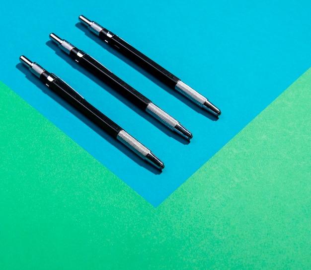 Strumenti minimalisti della penna sul fondo blu e verde dello spazio della copia Foto Gratuite