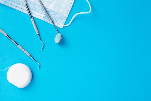 Strumenti o strumenti del dentista esploratori dentali, specchio dentale, filo interdentale e procedura maschera su sfondo azzurro. spazio libero. Foto Premium