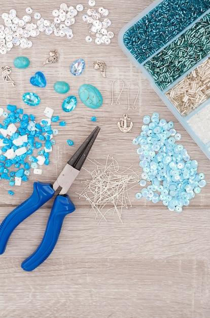 Strumenti per fare gioielli. cristalli, pendenti, ciondoli, pinza, cuori di vetro, scatola con perline e accessori su fondo in legno vecchio. Foto Premium