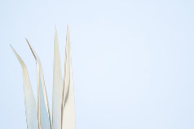 Strumenti per la procedura di estensione delle ciglia. due pinzette su sfondo blu Foto Premium