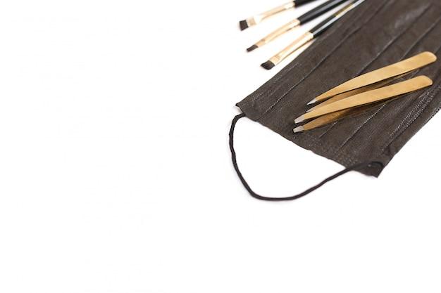 Strumenti per modellare le sopracciglia. maschera, pinzette, pennelli. vista dall'alto, posto per il testo. Foto Premium