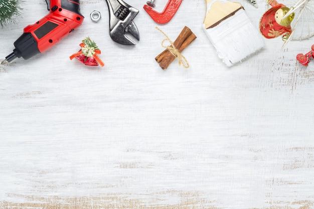 Strumenti utili della costruzione con l'ornamento di natale su legno bianco Foto Premium