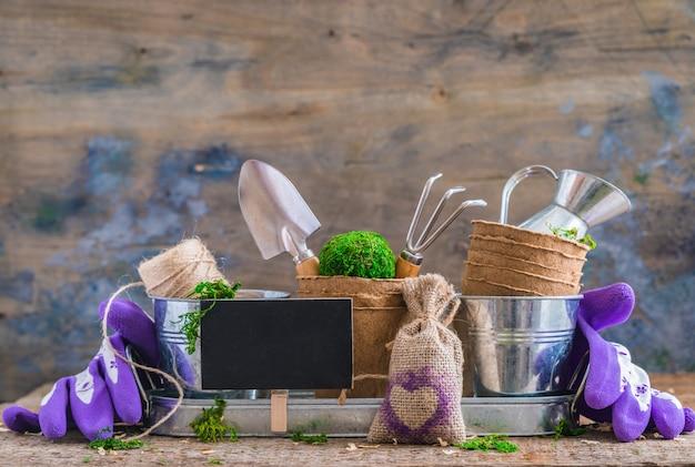 Strumenti, vasi e utensili di giardinaggio su fondo di legno rustico, con un bordo di gesso Foto Premium