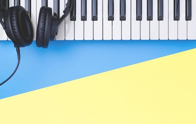 Strumento della tastiera di musica con la cuffia sullo spazio giallo blu della copia per il concetto di musica Foto Premium