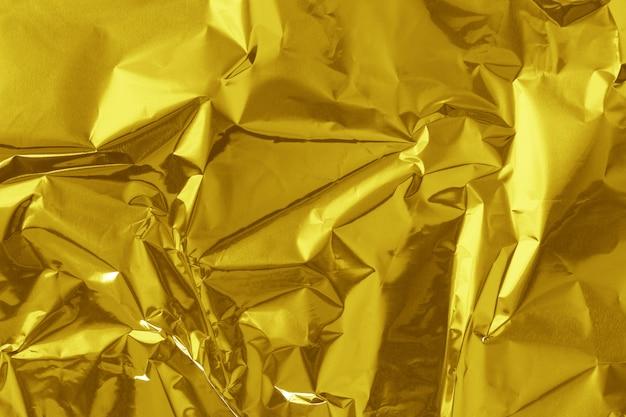 Struttura brillante della foglia della stagnola di oro, carta da imballaggio gialla astratta per fondo Foto Premium