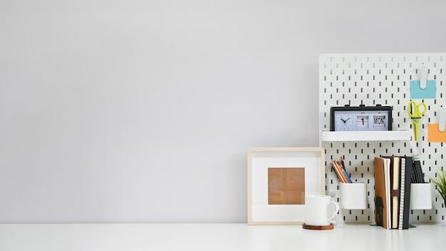 Struttura degli articoli per ufficio, del caffè e della foto dell'area di lavoro sulla tavola creativa bianca con lo spazio della copia. Foto Premium