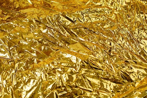 Struttura del fondo della foglia di oro con superficie irregolare sgualcita brillante Foto Premium