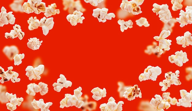 Struttura del popcorn, popcorn volante isolato su rosso Foto Premium