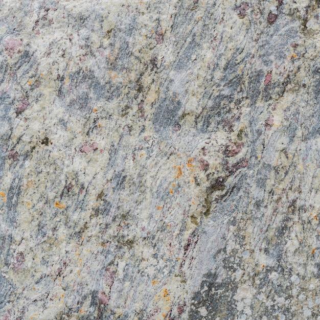 Struttura grigia di una pietra con macchie rosa. Foto Premium