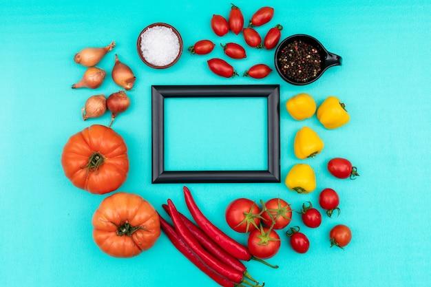 Struttura variopinta delle verdure circondata con pepe giallo dolce del sale marino della cipolla del pomodoro ciliegia del peperoncino rosso sulla superficie del blu Foto Gratuite