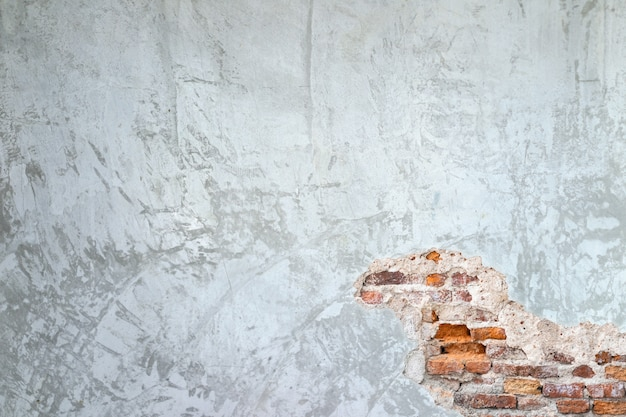 Strutturi il fondo delle pareti del cemento e delle crepe del vecchio mattone nella parete Foto Premium