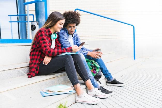 Studente adolescente delle coppie che si siede sulla scala bianca facendo uso del telefono cellulare Foto Gratuite