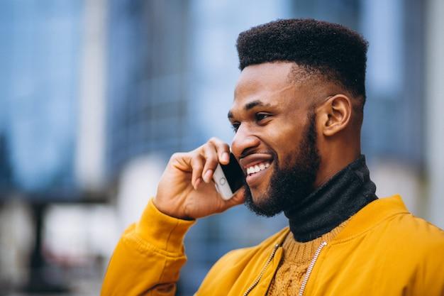 Studente afroamericano camminando per la strada e parlando al telefono Foto Gratuite
