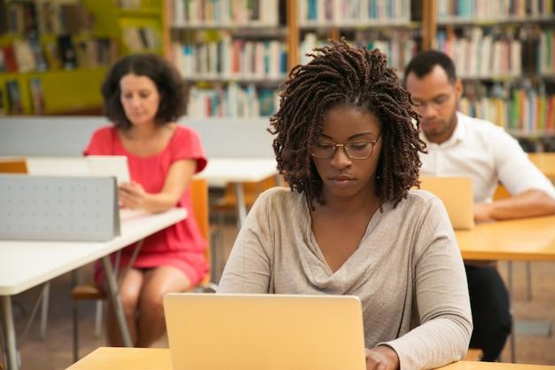 Studente afroamericano serio che studia nella biblioteca Foto Gratuite