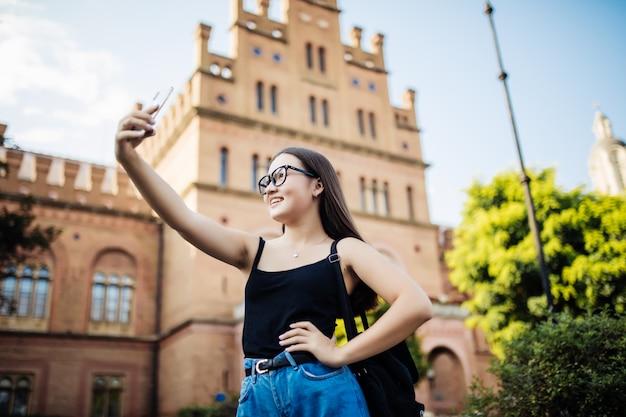 Studente asiatico che prende selfie nel campus Foto Gratuite